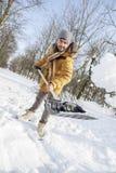 Hombre joven que traspala nieve cerca de una pequeña madera Fotografía de archivo