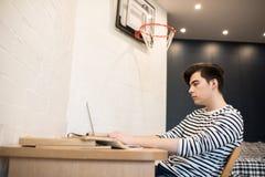 Hombre joven que usa el ordenador portátil en dormitorio fotografía de archivo