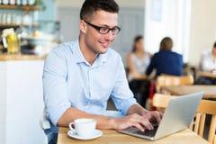 Hombre joven que usa el ordenador portátil en el café Imágenes de archivo libres de regalías