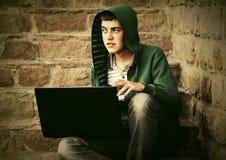 Hombre joven que usa el ordenador portátil en los pasos Fotografía de archivo