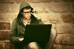 Hombre joven que usa el ordenador portátil en los pasos Foto de archivo libre de regalías