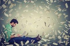 Hombre joven que usa el ordenador portátil que se sienta en el piso que construye el negocio en línea que hace el dinero Foto de archivo libre de regalías