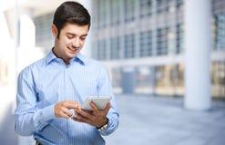 Hombre joven que usa el suyo tableta Imagen de archivo libre de regalías