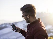 Hombre joven que usa el teléfono celular al aire libre en la moda del invierno Imagen de archivo libre de regalías