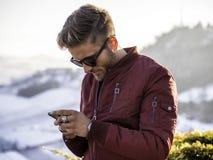 Hombre joven que usa el teléfono celular al aire libre en la moda del invierno Imagen de archivo
