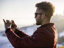 Hombre joven que usa el teléfono celular al aire libre en la moda del invierno Fotos de archivo libres de regalías