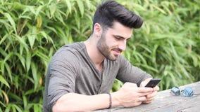 Hombre joven que usa el teléfono celular que se sienta en banco metrajes