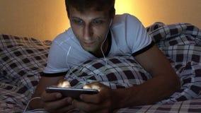 Hombre joven que usa el teléfono elegante que juega smartphone de los mensajes de texto del juego almacen de video