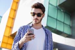 Hombre joven que usa el teléfono móvil Fotos de archivo libres de regalías