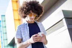 Hombre joven que usa el teléfono móvil Imagenes de archivo