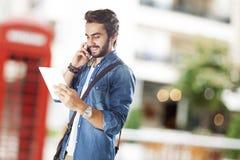 Hombre joven que usa el teléfono móvil en calle Fotografía de archivo