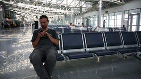 hombre joven que usa el teléfono móvil en el aeropuerto almacen de video
