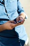 Hombre joven que usa el teléfono móvil en la calle Imágenes de archivo libres de regalías