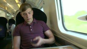 Hombre joven que usa el teléfono móvil en viaje de tren metrajes