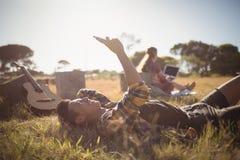 Hombre joven que usa el teléfono móvil mientras que miente en campo herboso Fotografía de archivo libre de regalías