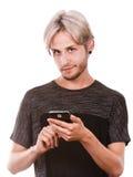 Hombre joven que usa el teléfono móvil que manda un SMS en smartphone Imagen de archivo