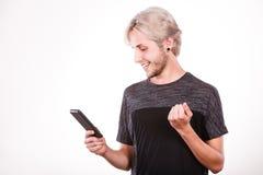 Hombre joven que usa el teléfono móvil que manda un SMS en smartphone Fotos de archivo libres de regalías
