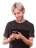 Hombre joven que usa el teléfono móvil que manda un SMS en smartphone Fotos de archivo