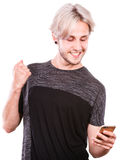 Hombre joven que usa el teléfono móvil que manda un SMS en smartphone Foto de archivo libre de regalías