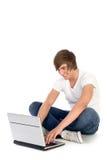 Hombre joven que usa la computadora portátil Imagen de archivo libre de regalías