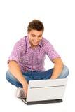 Hombre joven que usa la computadora portátil Fotografía de archivo