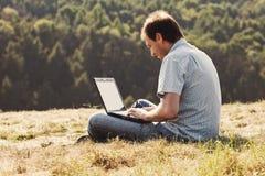 Hombre joven que usa la computadora portátil Foto de archivo