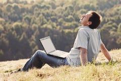 Hombre joven que usa la computadora portátil Imagen de archivo