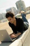 Hombre joven que usa la computadora portátil al aire libre Fotos de archivo libres de regalías