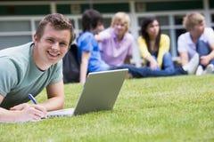 Hombre joven que usa la computadora portátil en césped del campus foto de archivo libre de regalías