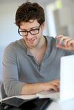 Hombre joven que usa la computadora portátil en el país Fotografía de archivo libre de regalías