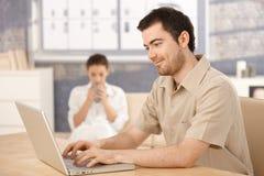 Hombre joven que usa a la mujer de la computadora portátil en el país en fondo Imagen de archivo