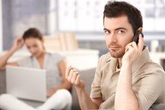 Hombre joven que usa a la mujer del móvil en casa en fondo imagen de archivo libre de regalías