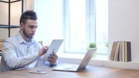 Hombre joven que usa la tableta en el trabajo almacen de metraje de vídeo