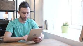 Hombre joven que usa la tableta en el trabajo metrajes
