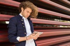 Hombre joven que usa la tableta en la calle Internet Foto de archivo libre de regalías