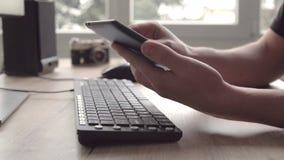 Hombre joven que usa la tableta mientras que sienta el teclado y el ratón de ordenador Funcionamiento del fotógrafo del Freelance metrajes