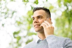 Hombre joven que usa la tableta y el teléfono móvil en el parque Fotos de archivo