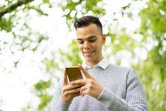 Hombre joven que usa la tableta y el teléfono móvil en el parque Imagen de archivo