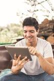 Hombre joven que usa la tablilla Foto de archivo libre de regalías