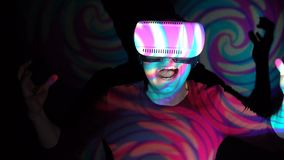 Hombre joven que usa las auriculares de la realidad virtual que gritan en el terror asustado metrajes