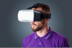 Hombre joven que usa los vidrios de las auriculares de VR imagenes de archivo