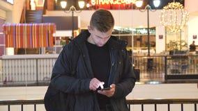 Hombre joven que usa smartphone en alameda de compras Información de la ojeada del individuo y enrollamiento de imágenes en el te almacen de metraje de vídeo