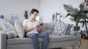 Hombre joven que usa Smartphone para hojear en línea almacen de metraje de vídeo