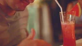 Hombre joven que usa smartphone y bebiendo el cóctel de la sandía en la barra de la noche que disfruta del momento 1920x1080 almacen de metraje de vídeo