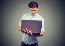 Hombre joven que usa su ordenador portátil Imagen de archivo libre de regalías