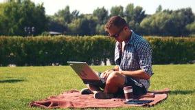 Hombre joven que usa su ordenador portátil al aire libre en el césped almacen de video