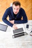 Hombre joven que usa su ordenador portátil en casa fotos de archivo