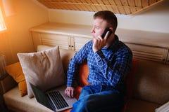 Hombre joven que usa su smartphone para las actividades bancarias en línea - sentándose en el sofá con el ordenador portátil en s imagenes de archivo