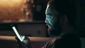 Hombre joven que usa su teléfono elegante en la oscuridad almacen de metraje de vídeo