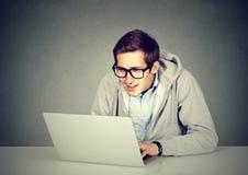 Hombre joven que usa un ordenador portátil que se sienta en la tabla Imagen de archivo